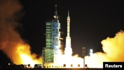 A modified model of the Long March CZ-2F rocket carrying an unmanned spacecraft blasts off from the launch pad at the Jiuquan Satellite Launch Center in northwest Gansu Province.