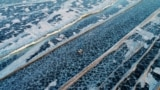 RUSSIA -- A car drives along a five-kilometre-long road, which is supervised by regional traffic services to connect the banks of the ice-covered Yenisei River during winter season, south of Krasnoyarsk, March 3, 2019