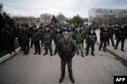 Українські офіцери перед виходом з військової бази, за воротами якої зібрались проросійсько налаштовані активісти, неподалік Севастополя, 6 березня 2014 року