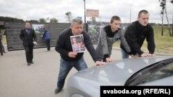 Аляксей Туровіч з постэрам свайго фільму «Жоўты пясочак» не прапускае транспарт у рэстарацыю каля Курапатаў 7 чэрвеня