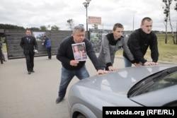 Аляксей Туровіч (зьлева) з постэрам свайго фільму «Жоўты пясочак» не прапускае транспарт у рэстарацыю каля Курапатаў 7 чэрвеня