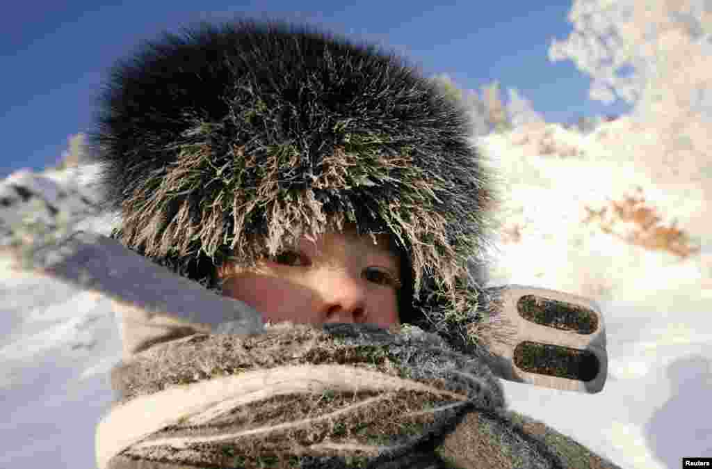 Frost covers the cap and scarf of a Russian child walking on a bank of the Yenisey River in air temperatures of about minus 30 degrees Celsius outside the Siberian city of Krasnoyarsk. (Reuters/Ilya Naymushin)
