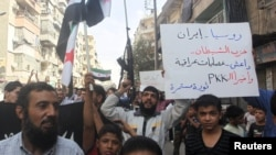 Residents carrying Free Syria Army flags chant slogans as they protest against Russian air strikes in Syria, in Aleppo on October 2.