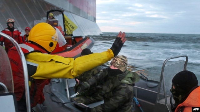 """In a Greenpeace handout photo taken on September 18, a Russian Coast Guard officer (center) wields a knife at an activist during a Greenpeace attempt to climb Gazprom's """"Prirazlomnaya"""" Arctic oil platform in the Pechora Sea."""