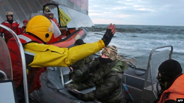 In this Greenpeace handout photo, a Russian Coast Guard troop holds a knife as activists try to climb Gazprom's 'Prirazlomnaya' Arctic oil platform in the Pechora Sea on September 18.