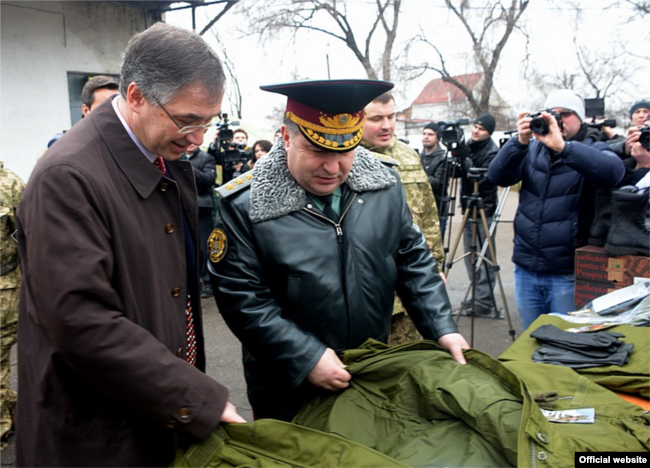 Посол Канади в Україні Роман Ващук та міністр оборони Степан Полторак оглядають одяг і взуття для бійців, військова частина на Одещині, 2 лютого 2015 року