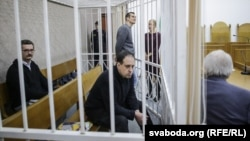 The three men on trial look on from the defendants' cage in a courtroom in Minsk on December 18.