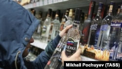 Мужчина рядом с полками с алкогольной продукцией в магазине.