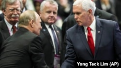 U.S. Vice President Mike Pence (right) shakes hands with Russian President Vladimir Putin during the 13th East Asian Summit Plenary on the sidelines of the 33rd ASEAN summit in Singapore on November 15.