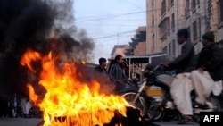 Tires burning during a protest in Karachi after the deadly attack.