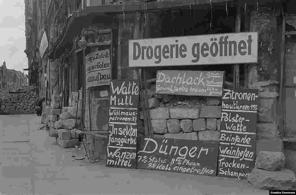 В края на 1945 г. животът в града продължава. Този магазин продава тоалетна хартия, ароматизатори и боя за стени.