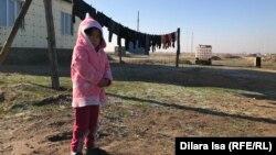 Девочка на фоне дома и емкости для воды в селе Катын Копир. 2 декабря 2018 года.