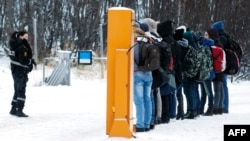 Працівниця поліції Норвегії інструктує мігрантів, які щойно прибули з Росії, фото 16 листопада 2015 року