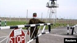 Пограничник закрывает шлагбаум на казахстанско-китайской границе, на контрольно-пропускном пункте «Хоргос».