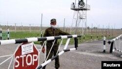 Пограничник в медицинской маске на пропускном пункте Хоргос на казахстанско-китайской границе.