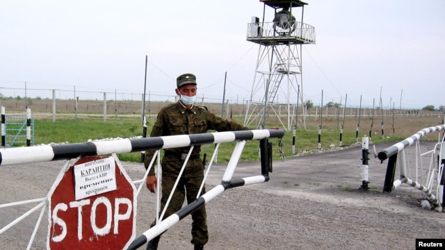 A Kazakh border guard closes a barrier at the Korgas crossing point, the largest on the 1,500-kilometer-long Kazakh-Chinese border.