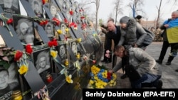 People place flowers at the memorial dedicated to people who died in the 2014 clashes with security forces on Kyiv's Independence Square on February 18, 2020.