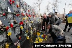 Az emberek virágot helyeznek el Kijevben, a Függetlenség terén, azaz a Majdanon Kijevben 2020. február 18-án, ahol az összecsapásokban meghalt emberek emlékműve áll.