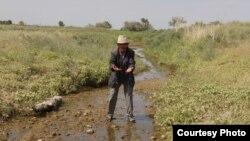 Житель села Кызылагаш Курманажи Ажибай на своем поле. 23 июля 2014 года.
