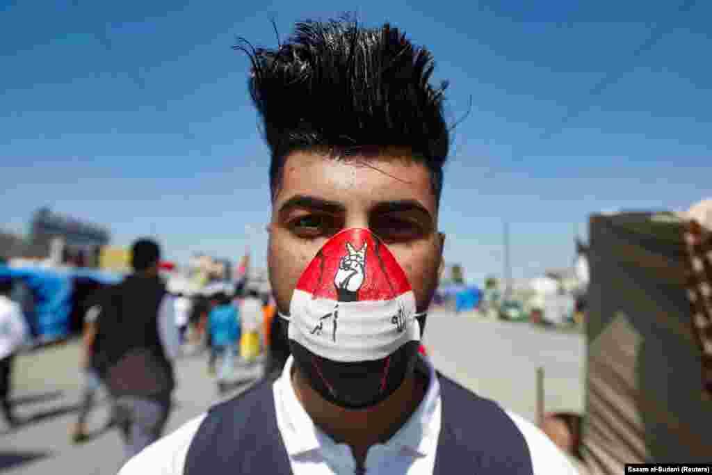 Ирактағы билікке қарсы наразылыққа коронавирусқа қарсы маскімен келгендердің бірі. Бұл елде 35 адам дертке шалдығып, екеуі бақилық болды. Басра қаласы, Ирак. 5 наурыз 2020 жыл.