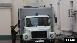 Полицейский готовит машину, чтобы увезти подсудимого бывшего вице-министра Аблая Сабдалина в следственный изолятор. Астана, 28 апреля 2010 года.