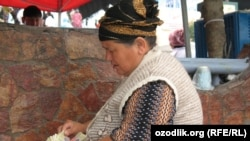 Uzbekistan - a businesswoman is counting money in one of the Uzbek bazaars in Tashkent, undated