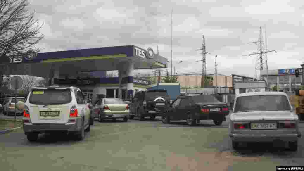 На АЗС черги, люди заправляють машини, заливають бензин у каністри, запасаючись паливом для генераторів