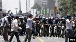 Basij militia members on motorcycles face off against protesters in Tehran in July 2009.