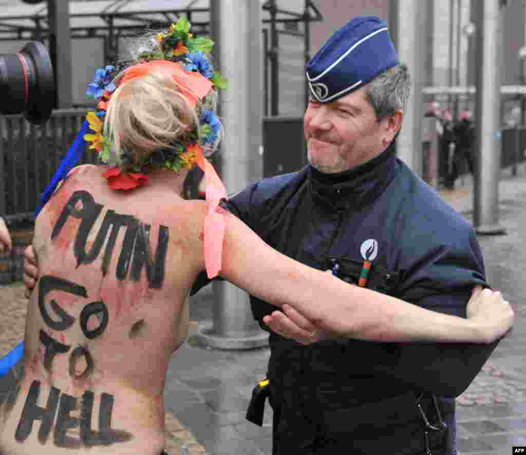 An activist of Ukraine's Femen feminist group is taken away by police as she demonstrates near the EU Council building in Brussels, where an EU-Russia summit was being held. (AFP/Georges Gobet)
