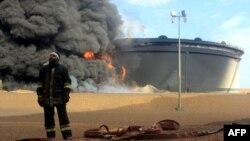Ливийский пожарный у горящего нефтехранилища на севере страны в районе Рас-эль-Ануф (архив)