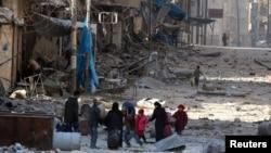 Люди в Сирии посреди разрушенных зданий.