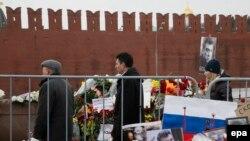 Мәскеу орталығындағы Борис Немцовқа қастандық жасалған жерге гүл шоқтарын қойып жатқан адамдар. Мәскеу, 2 наурыз 2015 жыл.