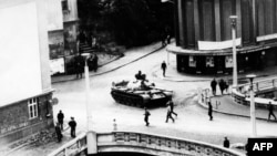 A tank drives on a street in the Czechoslovak city of Trutnov during confrontations between demonstrators and Warsaw Pact troops and tanks in August 1968.