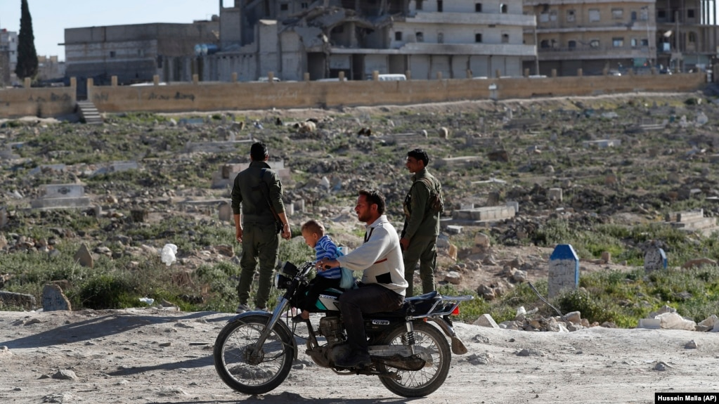 a syrian man and his kids ride a motorcycle in manbij earlier this year