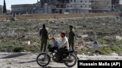 A Syrian man and his kids ride a motorcycle in Manbij earlier this year.