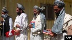 Толибони таслимшуда бо нусхаи Қуръон дар даст ба сафҳои артиши афғон шомил мешаванд