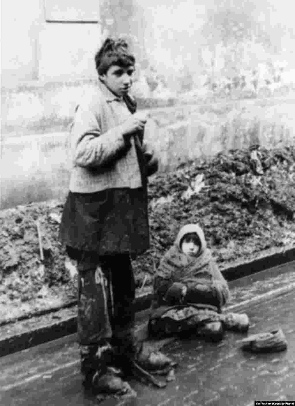 A young woman and a girl beg in the street.