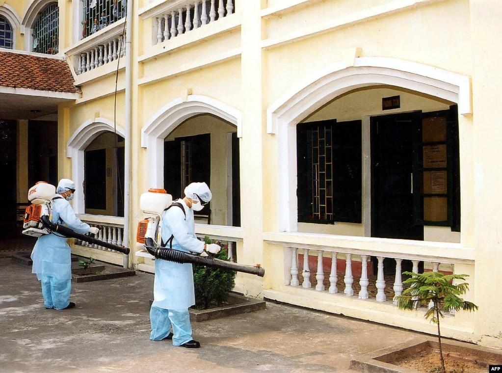 Ханой маңындағы аурухана аумағын дезинфекциялап жүрген медицина қызметкерлері. Вьетнам, 2003 жылдың сәуірі.