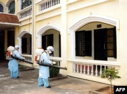 Medical workers disinfecting the grounds of a hospital near Hanoi, Vietnam, in April 2003.