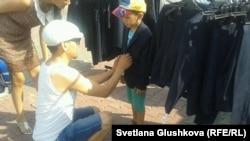 Мальчику примеряют школьную форму на школьной ярмарке. Астана, 23 августа 2014 года.