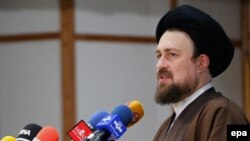 Hassan Khomeini, the grandson of late Iranian Supreme Leader Ayatollah Ruhollah Khomeini, speaks to reporters after registering his application to run for the Assembly of Experts on December 18.