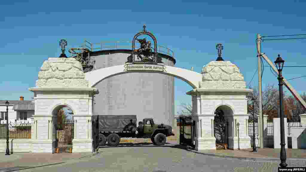 Ворота на входе в парк у мыса Фиолент. Мимо проезжает военная машина
