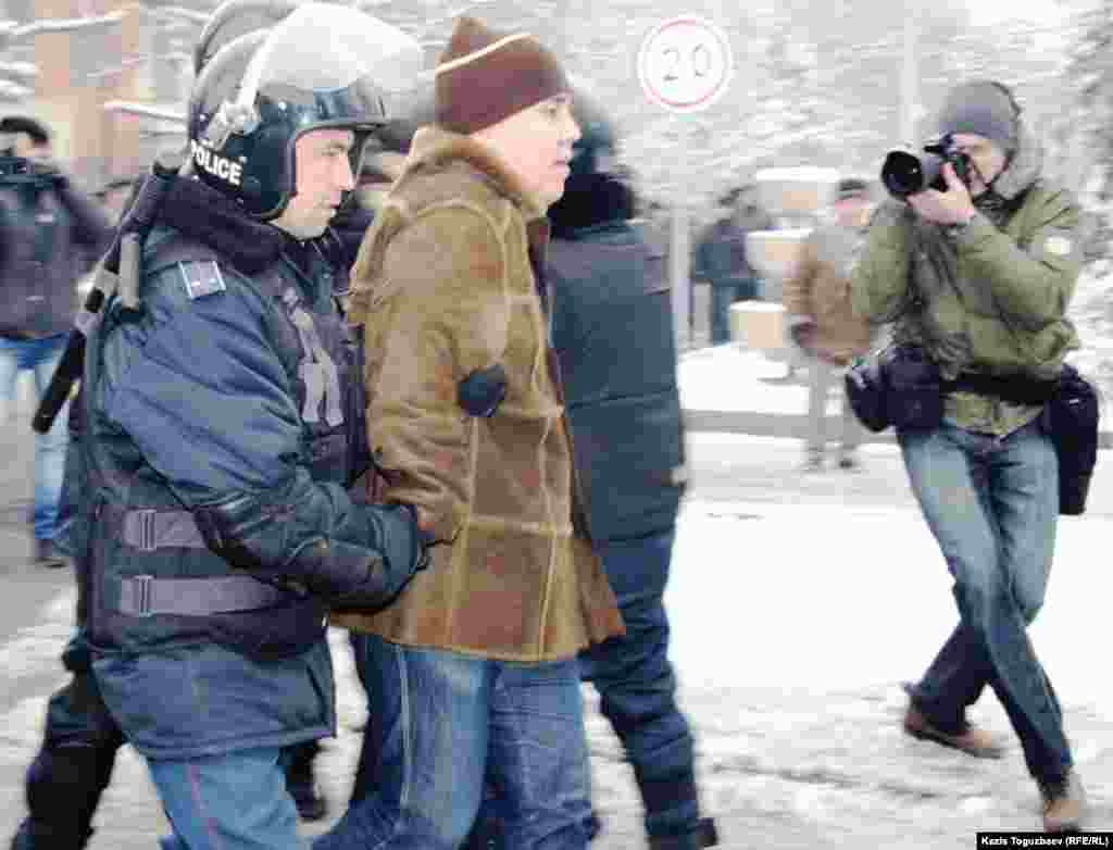 Полицейские задерживают людей, решивших выразить протест действиям властей в Жанаозене во время массовых беспорядков 16 декабря 2011 года.