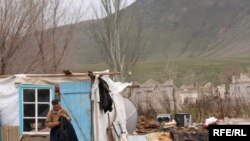 A Kazakh man lives in makeshift housing after fleeing floods earlier this spring.