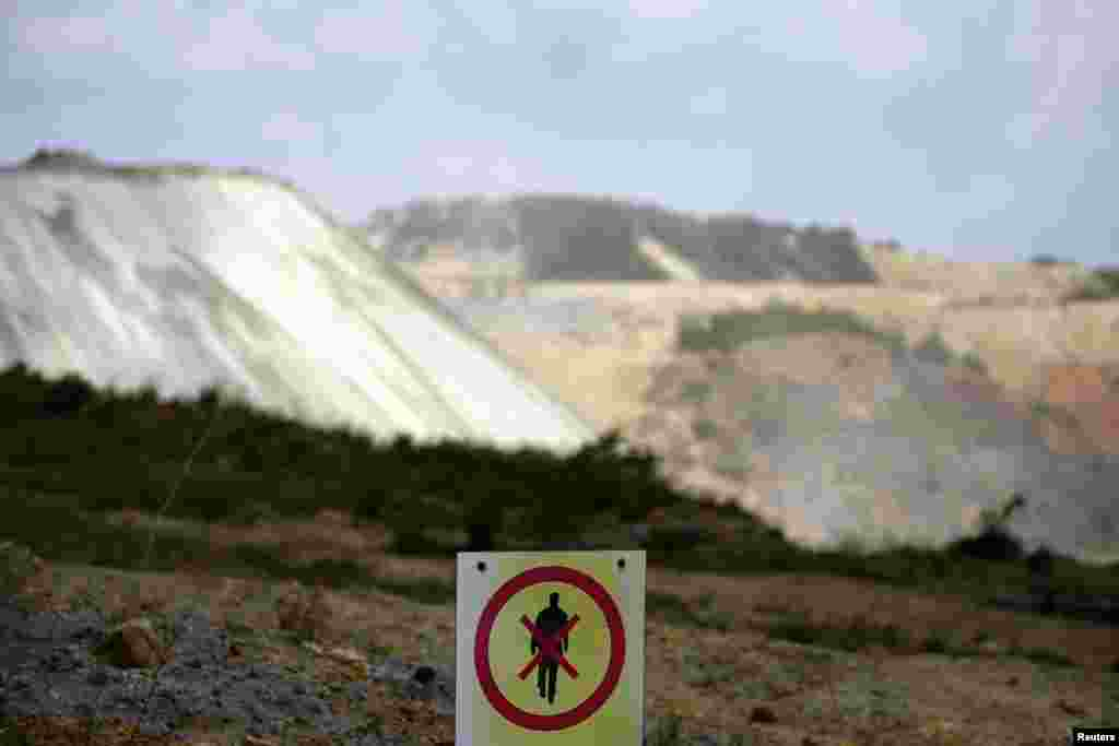 A no-trespassing sign marks the boundary of the open copper pit.