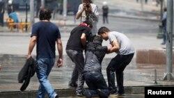 Протестующие в Анкаре помогают своему товарищу, попавшему под удар струи водомёта. Анкара, 16 июня 2013 г.