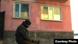 Житель города греется на улице у костра возле дома в Приозерске. Январь 2011 года.