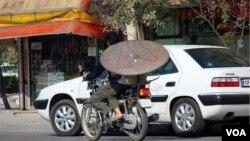 Иранский мужчина везет спутниковую антенну на мотоцикле.