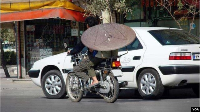 An Iranian man on a motorcycle carries a satellite dish. (file photo)
