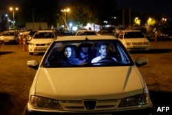 Iranians sit in their cars while taking part in a religious ceremony during the holy month of Ramadan in a parking in Tehran.